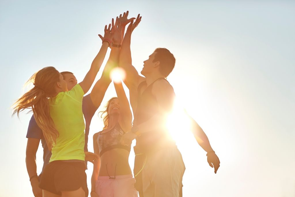 Athletes high fiving after successful workout